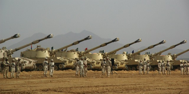 Saudi soldiers stand at attention in front of tanks during a visit by Deputy Defence Minister Prince Khaled bin Sultan (unseen) at Al-Khoba in the southern Jizan province near the border with Yemen on January 27, 2010. Sultan said that Yemeni Shiite rebels were chased out of the kingdom and did not pull out on their accord as they claim. The leader of Shiite rebels, known also as Huthis, had announced on January 25 the voluntary withdrawal of his fighters from positions occupied within Saudi Arabia. AFP PHOTO/STR (Photo credit should read -/AFP/Getty Images)